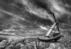 Old anchor at a stormy beach.