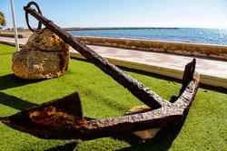 Old anchor on a promenade of Santa Pola, Alicante. Mediterranean sea on background.