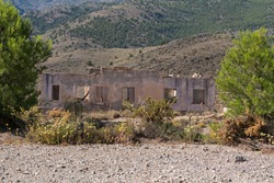 Old and abandoned building in a mining complex, the building has windows and doors, there are pine trees next to the building, there is pine forest in a mountainous area