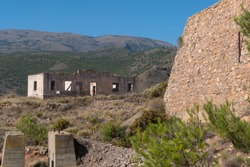 Old and abandoned buildings in a mining complex, the buildings are built in bricks, there is a stone wall, it is a mountainous area and the sky is clear