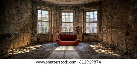Old and abandoned room with three big broken windows and a red couch