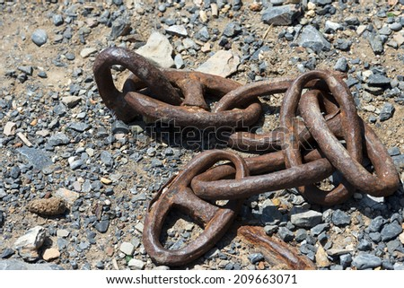 Old and Abandoned Rusty Chain / Old rusty chain for mooring abandoned on the ground with gravel