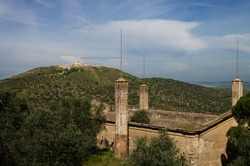 Old and abandoned Santa Barbara ammunition depot just outside Elvas walls along with the view of Graca fortress hill on the background. Clouded blue sky. Portugal.