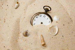 Old and antique vintage clock pocket watch in the sand of a beach without pointers, symbolizes the concept of no time or timeless, no rush, end of time or everlasting and forever, deadline