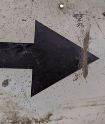 old and black metal arrow sign points to the right