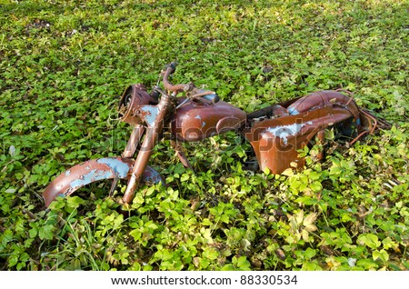 old and broken motorcycle in the autumn grass