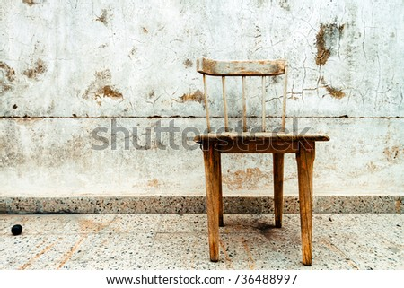 Old And Broken Wooden Chair With Cracked Wall Background On A Terrace 736488997