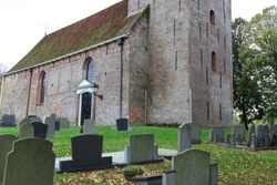 old and characteristic Dutch cemetery near a church. photo was taken on a autumnal and cloudy day.