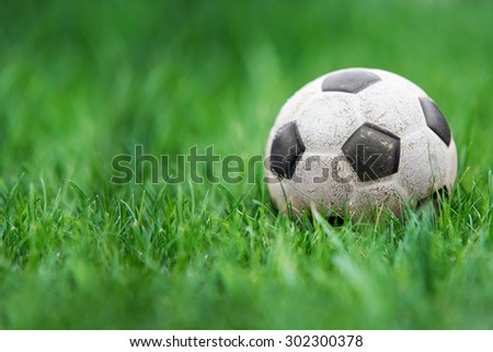 Old and classic Soccer ball or football ball on green field