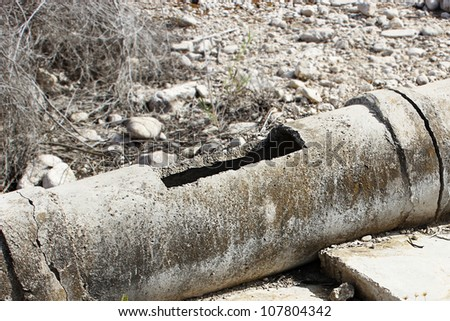 Old and cracked concrete pipe for watering.