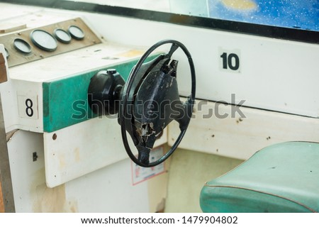Old and damage steering wheel and dashboard of white speedboat. Damaged speedboat is parking on the river. White speedboat damaged. #1479904802