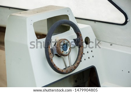 Old and damage steering wheel and dashboard of white speedboat. Damaged speedboat is parking on the river. White speedboat damaged. #1479904805