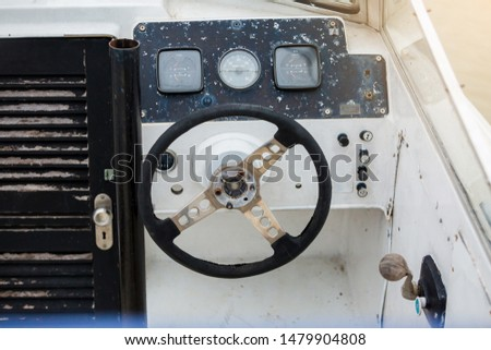 Old and damage steering wheel and dashboard of white speedboat. Damaged speedboat is parking on the river. White speedboat damaged. #1479904808