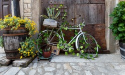 Old and decorative bicycle leaning against old wooden door at  traditional village in Spain