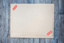 Old and dirty brown paper big size envelope on wooden background marked red DO NOT BEND, mail postage shipping business papers, documents and fragile items concept