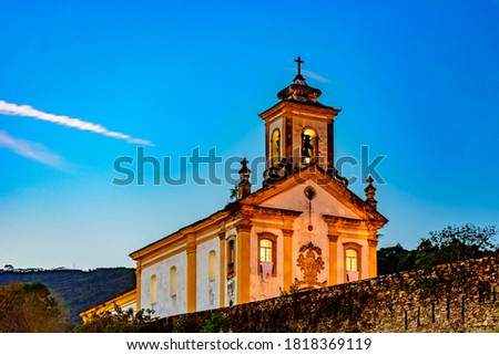 Old and historic 18th century church with its facade illuminated at dusk in the city of Ouro Preto, Minas Gerais, Brazil Foto stock ©