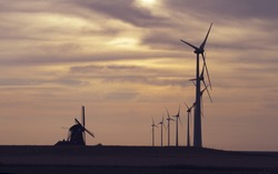 Old and new - old windmill and wind turbine on the field, sunset, Holland, Netherlands, Europe