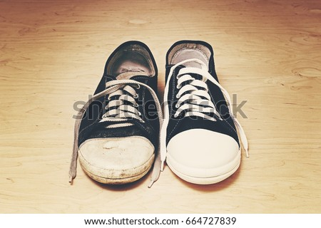 Old and new sneakers with white laces on light wooden background #664727839