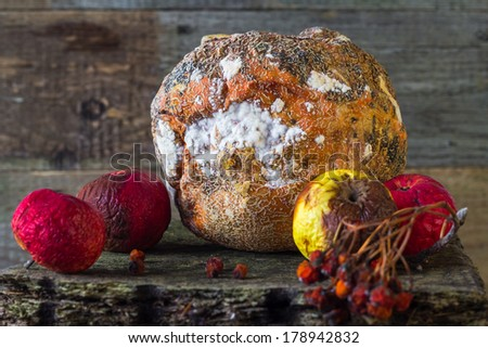 Old and rotten fruit on wooden board - stock photo