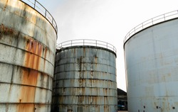 Old and rusted steel silos for storage of solids and liquids.