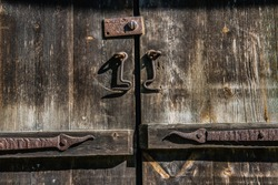 Old and rusty hook locks the old dried up wooden barn door.
