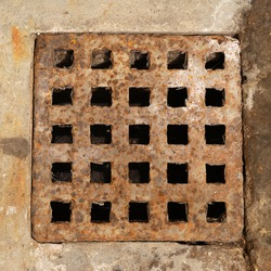 Old and rusty metal sewer lid