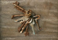 Old and rusty ring of keys on wood