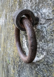 Old and rusty steel mooring ring attached to a stone wall.