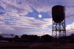 Old and rusty water tower on a blue sky and moon background.