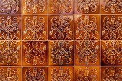 Old and traditional portuguese ceramic tile panels with relief ornamental motifs in brown tones, bright decorated and glazed tiles. Ornamental background texture pattern.