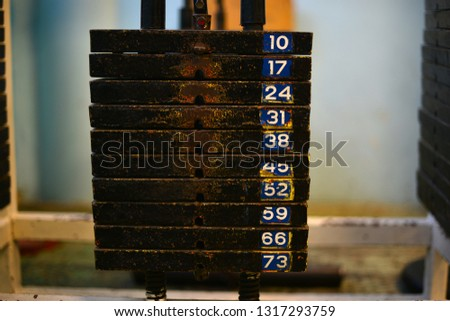 Old and used a weight stack with the gym. Rusty flat metal weights. Weighting material.
