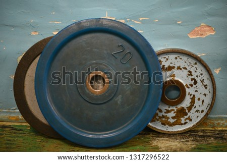 Old and used a weight stack with the gym. Rusty flat metal weights. Weighting material. Fitness room. Sporting equipment. Many weight plates in the gym.
