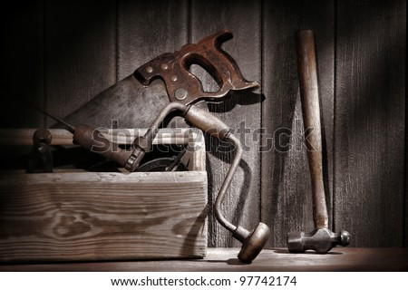 Old and used antique carpenter and handyman tools with drill and crosscut saw and hammer in an aged rustic wood toolbox in a vintage carpentry workshop