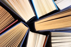 Old and used hardback books or text books seen from above. Books and reading are essential for self improvement, gaining knowledge and success in our careers, business and personal lives