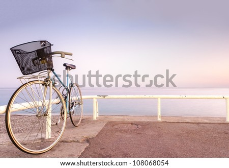 Old and vintage bicycle at the railing near the sea. Blue sea and sunset sky in background. A lot of copy space. Nice, France, Europe.