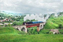 Old and vintage steam train with blue coaches crossing ancient bridge on the green mountain pass. Beautiful landscape and tourist train with unique steam loco like like a fairy tale