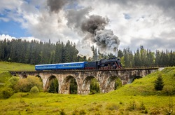 Old and vintage steam train with blue coaches crossing ancient stone bridge on the green mountain pass. Beautiful landscape and nostalgic train with unique and epic steam loco like like a fairy tale