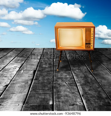 Old and Vintage Television on Perspective Old Wood Texture in Front of Blue Sky and White Cloud.