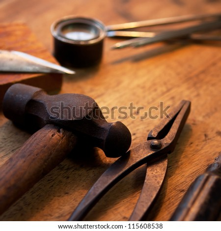 Old and well used hammer, pliers and screw driver on a old wooden desk. With warm incandescent  lighting.