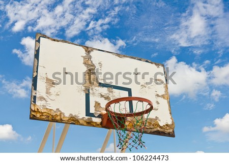 Old and worn basketball board against blue sky
