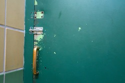 Old and worn green painted metal door with sliding bolt closure and brassy metal handle.