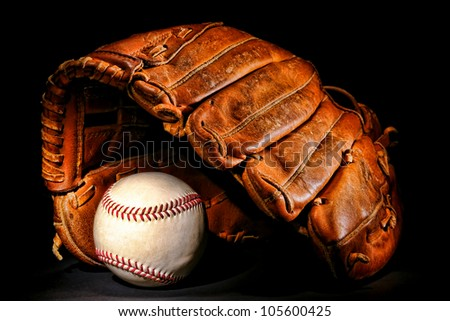 Old and worn used leather baseball catcher sport glove over aged regulation professional stitched ball on black