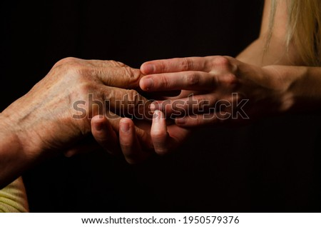 Old and young hands close up. Respect for the elderly. Grandmother's wrinkled hands. The granddaughter touches the wrinkles on the old hands of the grandmother. Young and old hands together. Force Foto d'archivio ©