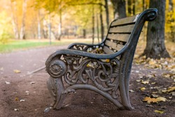 Old antique cast-iron retro bench with wooden planks in the autumn park. It's nice to sit down and enjoy the extraordinary natural beauty of the autumn forest.