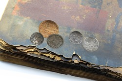 Old antique collectible coins and old book with shabby pages close-up isolated on white background as vintage antique still life for advertising antique shop or museum