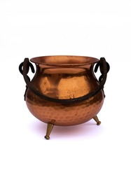 Old antique copper / bronze pot / cauldron / kettle with black holder and three small legs isolated on white studio background
