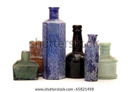 Old antique glass bottles in different colours on a white background. / Antique bottles
