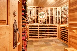 Old antique key lock door know details. Bright home wine cellar with wooden storage units and arch with bottles. Northwest, USA