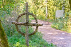 Old antique medieval wooden celtic cross by the road in a forest