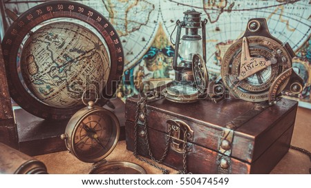 Old antique rare items collections including with a compass, oil lamp, globe model rotation on a wooden base and treasure chest of pirate and sailing on the ocean. (vintage style)  #550474549